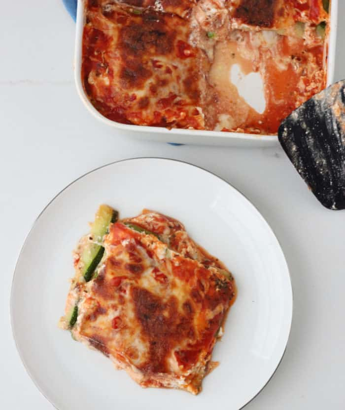 white plate with slice of Zucchini Lasagna with a casserole dish of lasagna and spatula