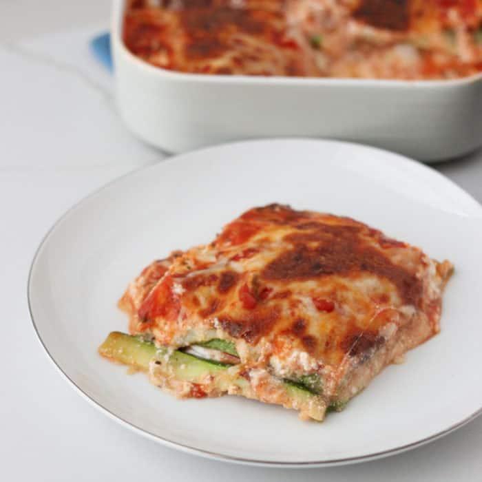 white plate of zucchini lasagna with casserole dish of lasagna