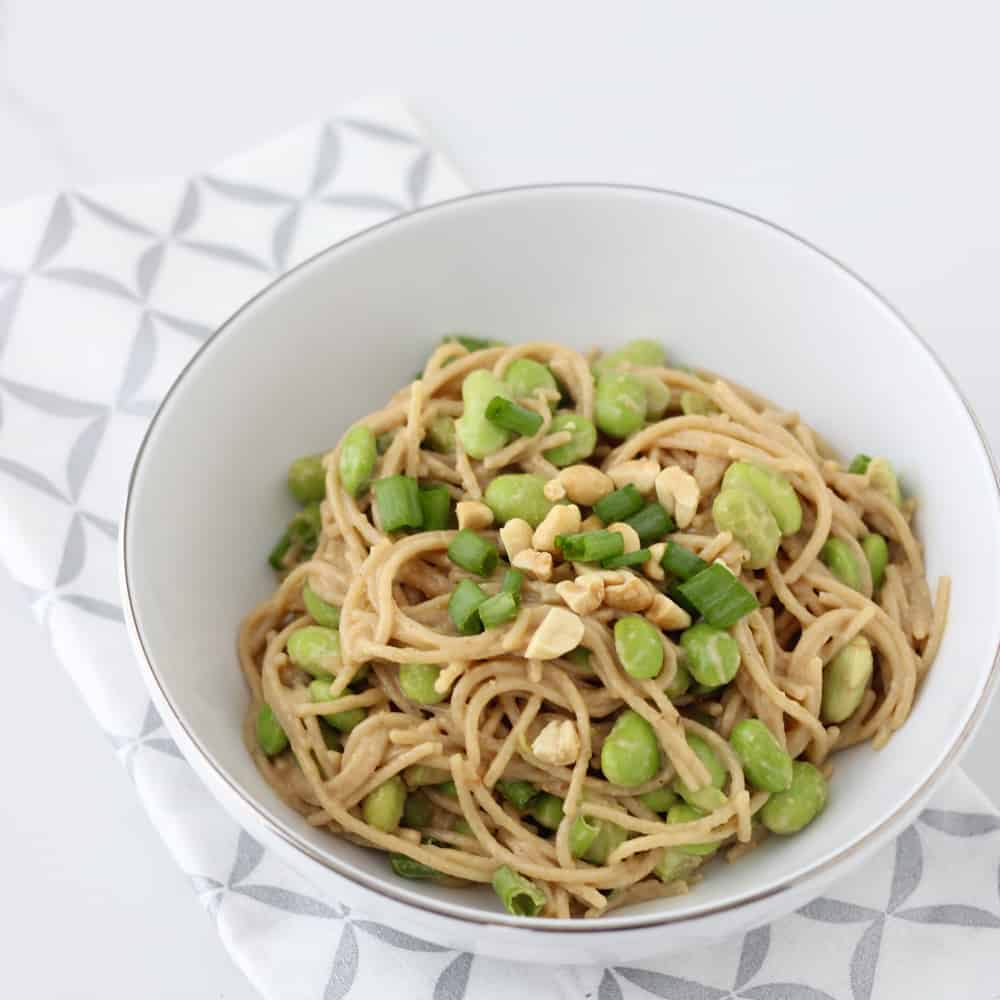 bowl of peanut pasta made in the microwave in a white bowl on a silver and white napkin