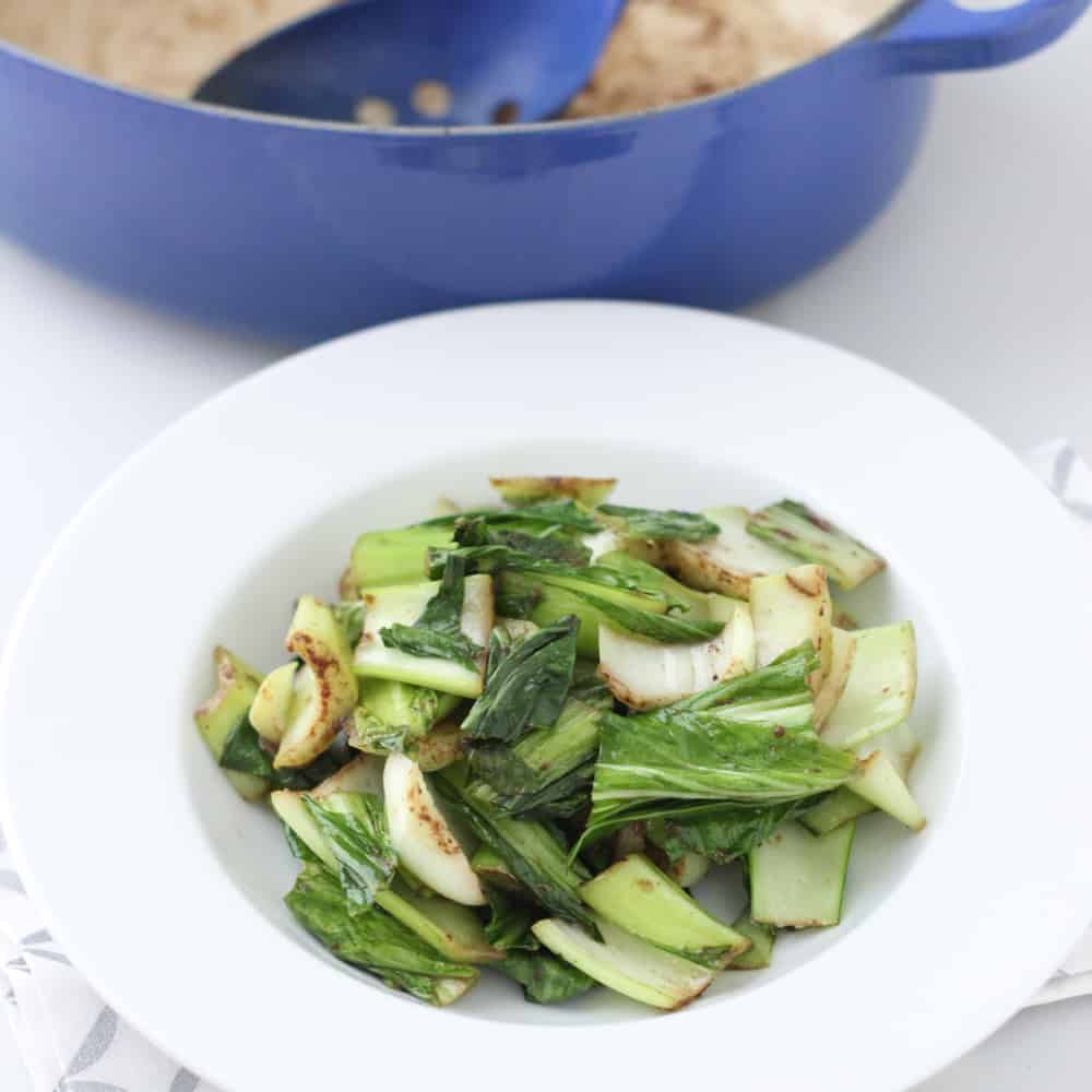 white bowl of Five Spice Bok Choy with dutch oven in background