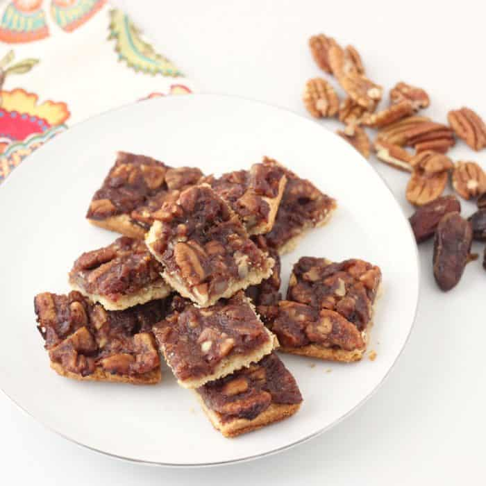 white plate of pecan pie bars, pecans and dates