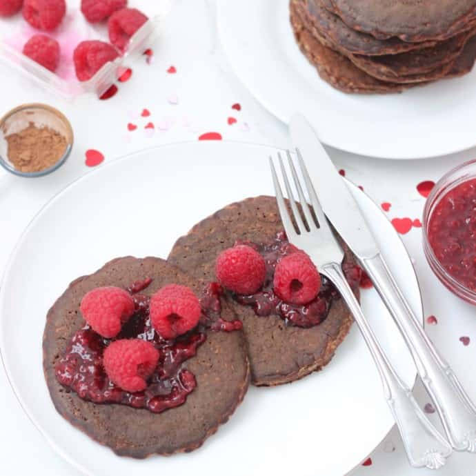 two Chocolate Protein Pancakes with raspberries and raspberry sauce on a white plate with fork and knife and valentines day confetti l;;;