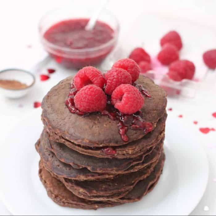 stack of chocolate protein pancakes with raspberries and raspberry sauce on top and in background