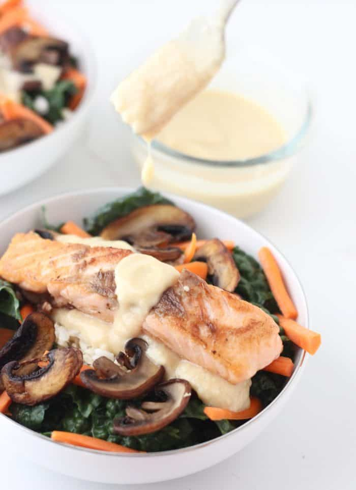 Miso Dressing drizzled from a fork onto a bowl of salmon, kale, mushrooms, carrots and brown rice