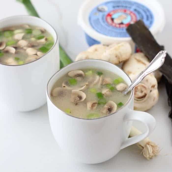 mug of miso soup with green onions, button mushrooms, and miso paste