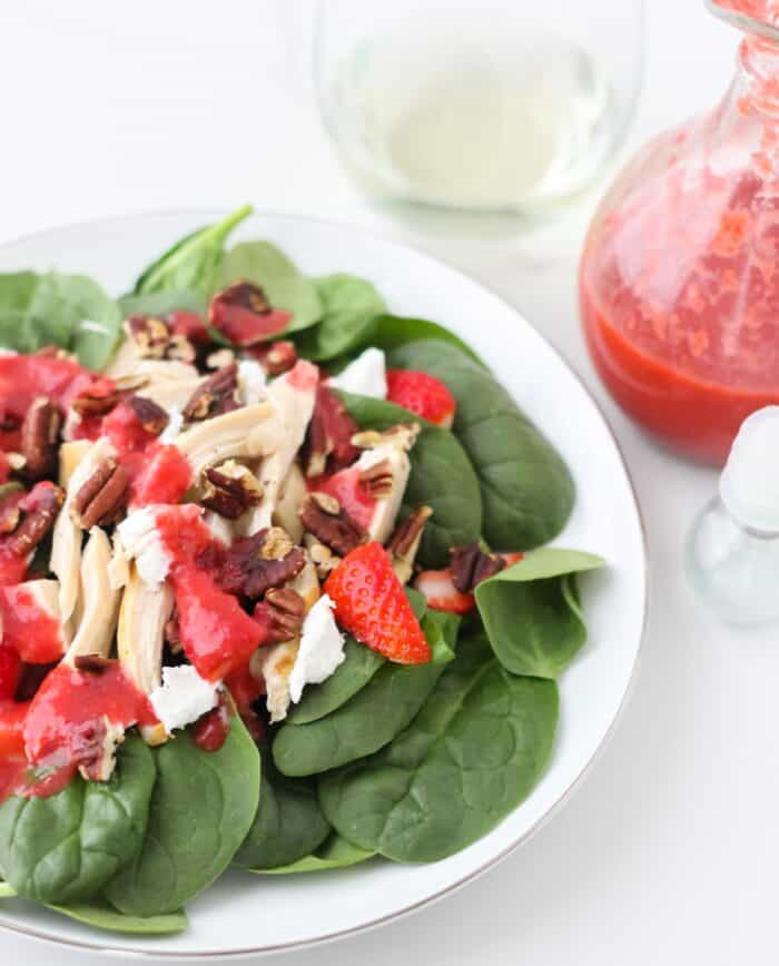 plate of spinach, pecan and goat cheese salad covered in strawberry salad dressing with a glass of white wine