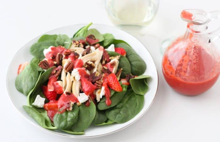 bottle of salad dressing, plate of spinach salad with pecans, feta and strawberries
