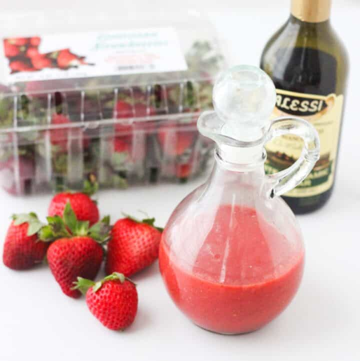 fresh strawberries on white counter with glass container of strawberry dressing, jar of balsamic vinegar