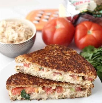 Chicken Salad Grilled Cheese on white plate with tomatoes, chicken salad, cheese grater, parsley