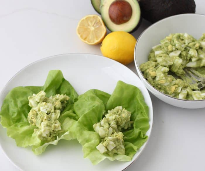 two lettuce wraps with avocado egg salad, bowl with salad, lemon, avocado
