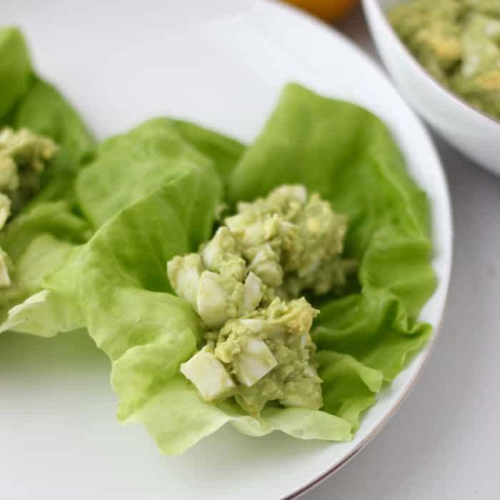 lettuce with avocado egg salad on white plate