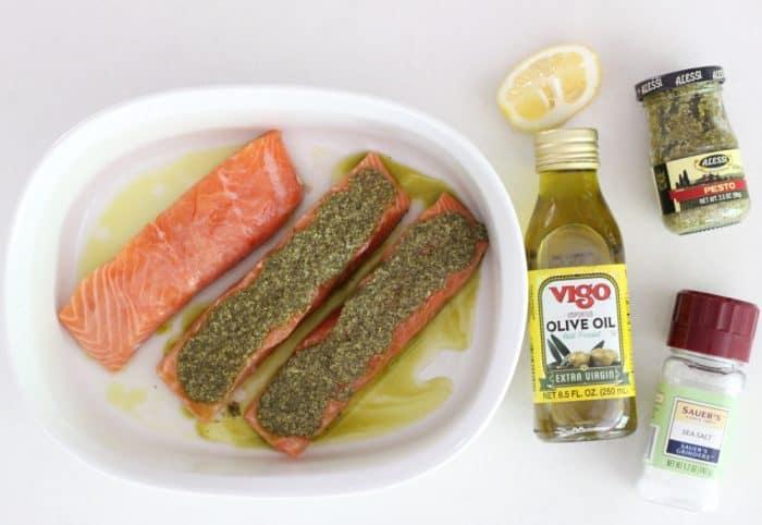 lemon, olive oil, pesto, salt, three salmon fillets in white baking dish covered with pesto