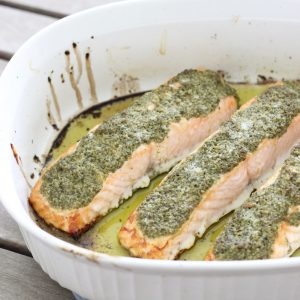 salmon fillets covered in pesto in a white baking dish on wooden table