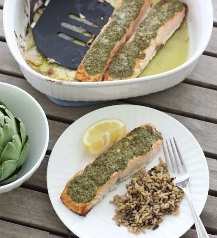 artichoke in white bowl, salmon, lemon slice, and wild rice on white plate, pesto covered salmon and spatula in white baking dish