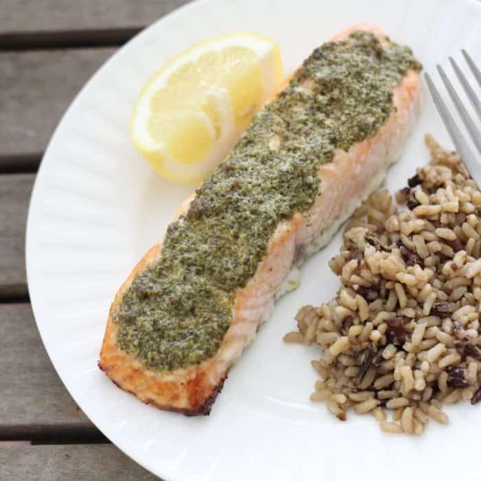 lemon slice, Pesto covered Salmon, wild rice, fork on white plate