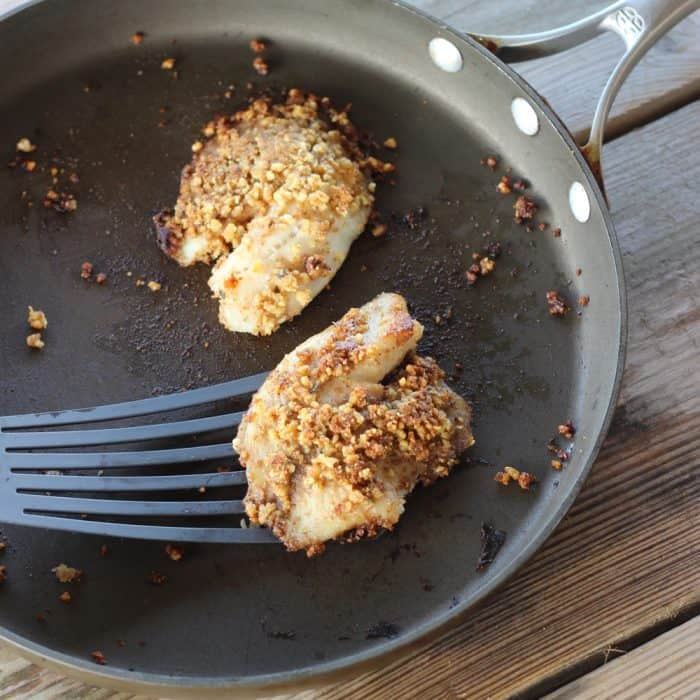 spatula lifting Walnut Crusted Fish out of a skillet on wooden table