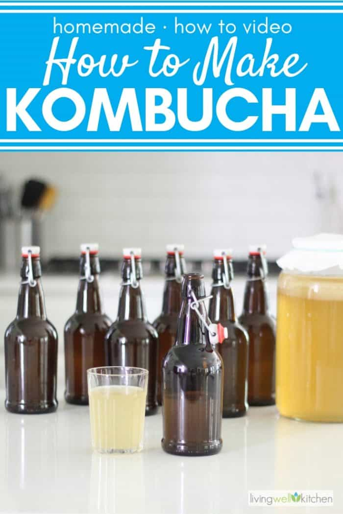 bottles of kombucha on white counter with glass of kombucha in clear glass