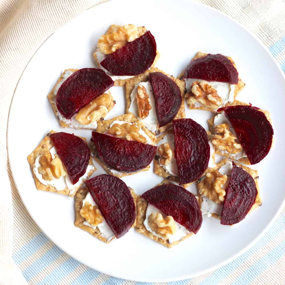 plate of Roasted Beet and Goat Cheese Crackers with walnuts on blue and cream towel