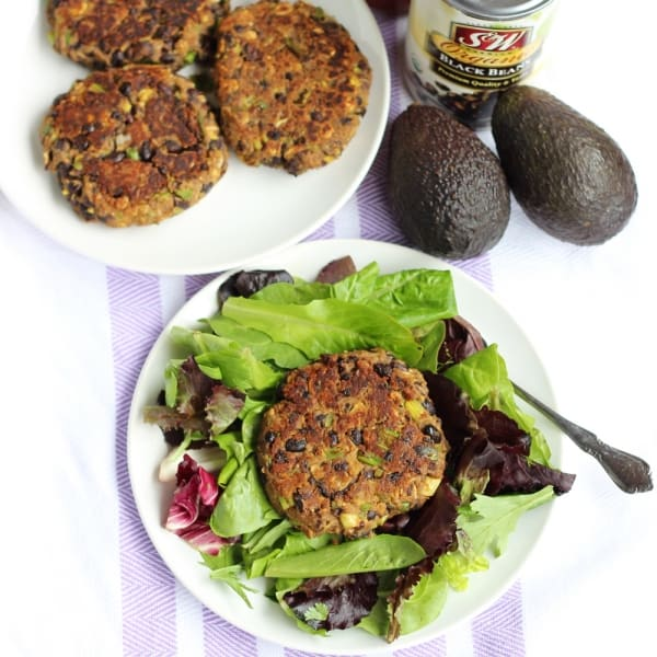 plate of avocado black bean burgers with avocados, black beans and salad with burger on top