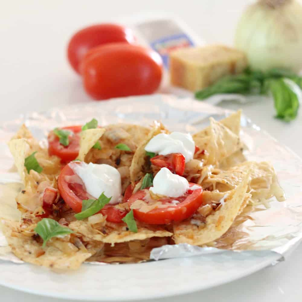 plate of Tomato Basil Nachos with tomatoes, cheese and basil in background