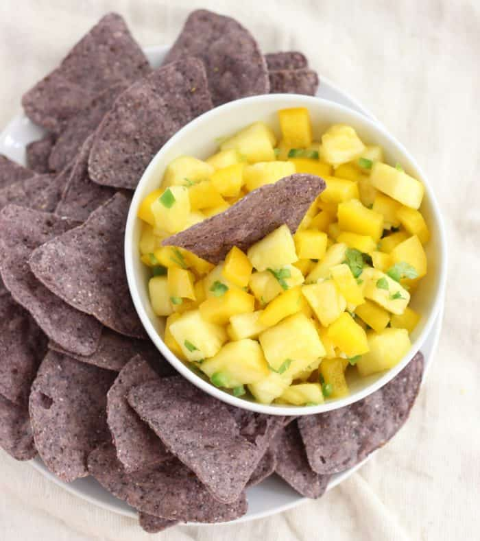 A sweet and spicy salsa served as a dip with blue corn chips for a festive football snack. Pineapple Salsa is a fresh and healthy way to add flavor to your day that's gluten free and vegan. This recipe is also delicious served over cooked fish or chicken as well as in tacos or over eggs.