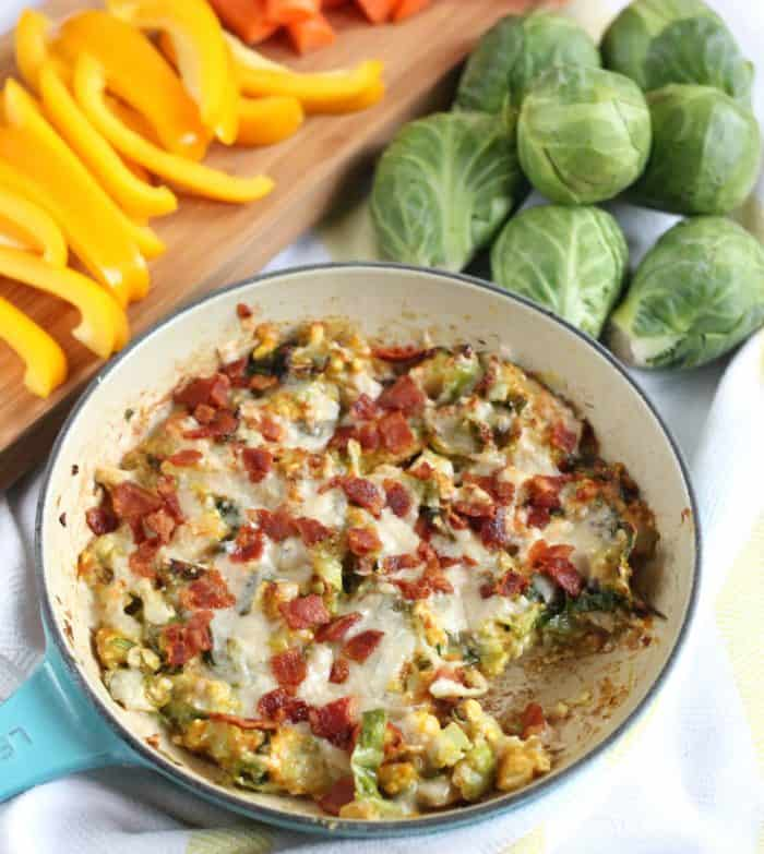 skillet of Cheesy Brussels Sprouts Dip with bell peppers on wooden cutting board and fresh Brussels sprouts