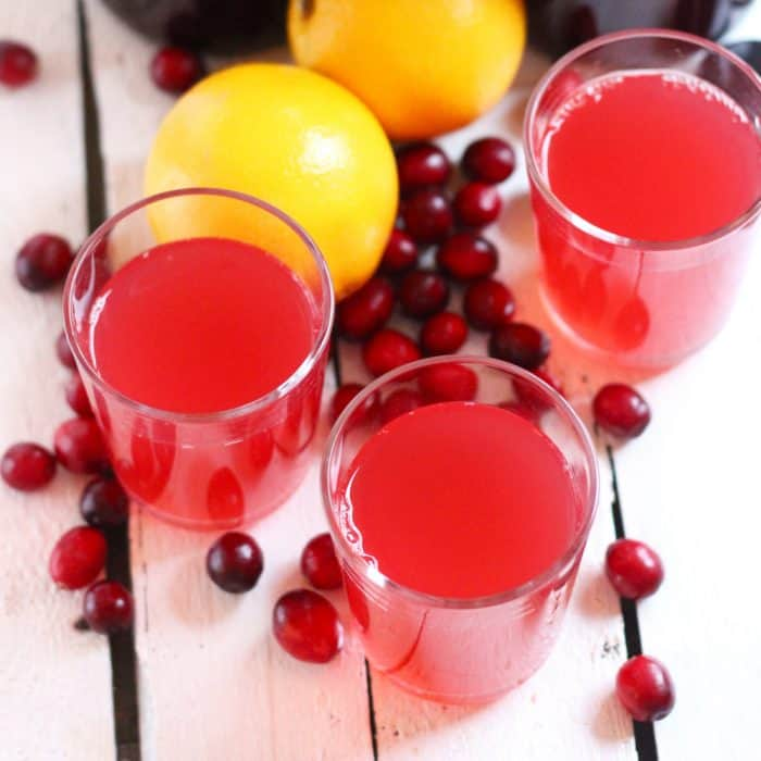 glasses of Cranberry Orange Kombucha with fresh cranberries and oranges
