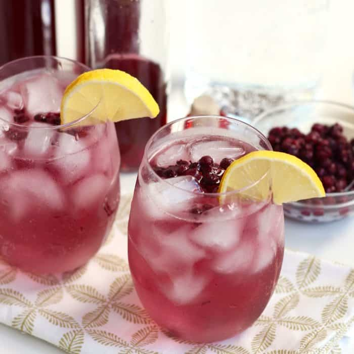 two purplish-blue cocktails made with homemade wild blueberry lemon vodka and garnished with lemon slices, frozen wild blueberries