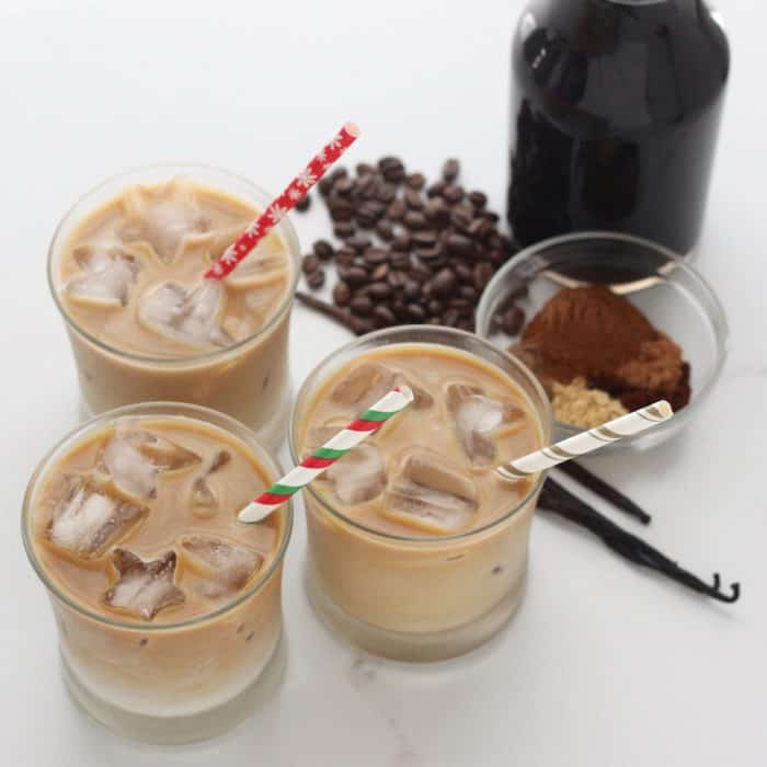 cold brew Gingerbread Coffee, iced gingerbread coffees with Christmas straws, spices, vanilla beans and coffee beans
