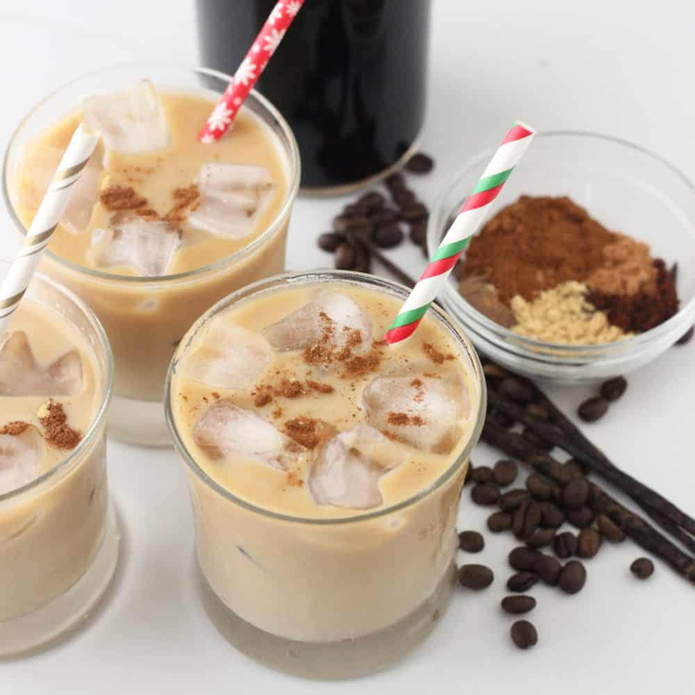 3 glasses of Gingerbread iced Coffee with Christmas straws, coffee beans, vanilla beans, spices