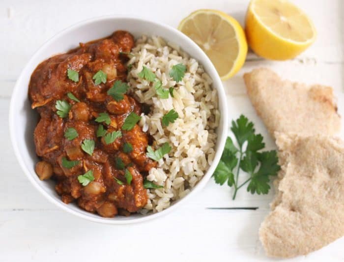 bowl of Chicken Tikka Masala and rice with cut lemon and pieces of naan