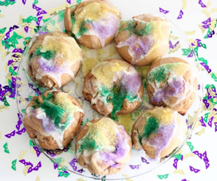 mini king cakes on clear plate with mardi gras confetti