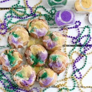 mini king cakes on clear plate with green, purple, yellow beads and colored sugar