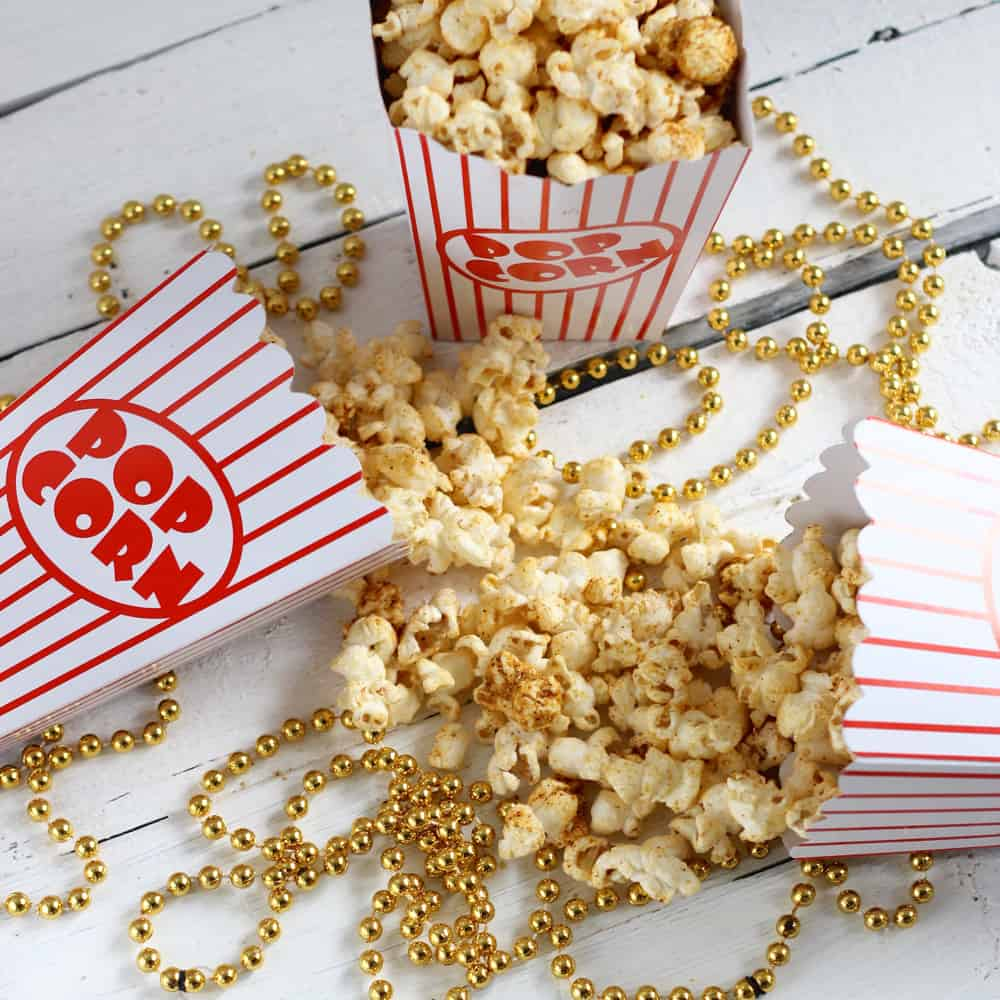 "popcorn containers with vegan ""Cheesy"" Taco Popcorn on a background of gold beads"