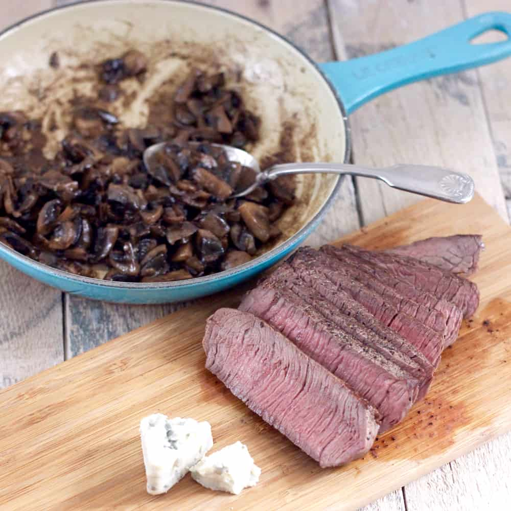 sliced Steak on cutting board with blue cheese and Mushroom Sauce in a skillet