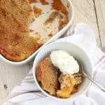 white bowl of peach cobbler with ice cream and spoon on towel with baking dish of cobbler