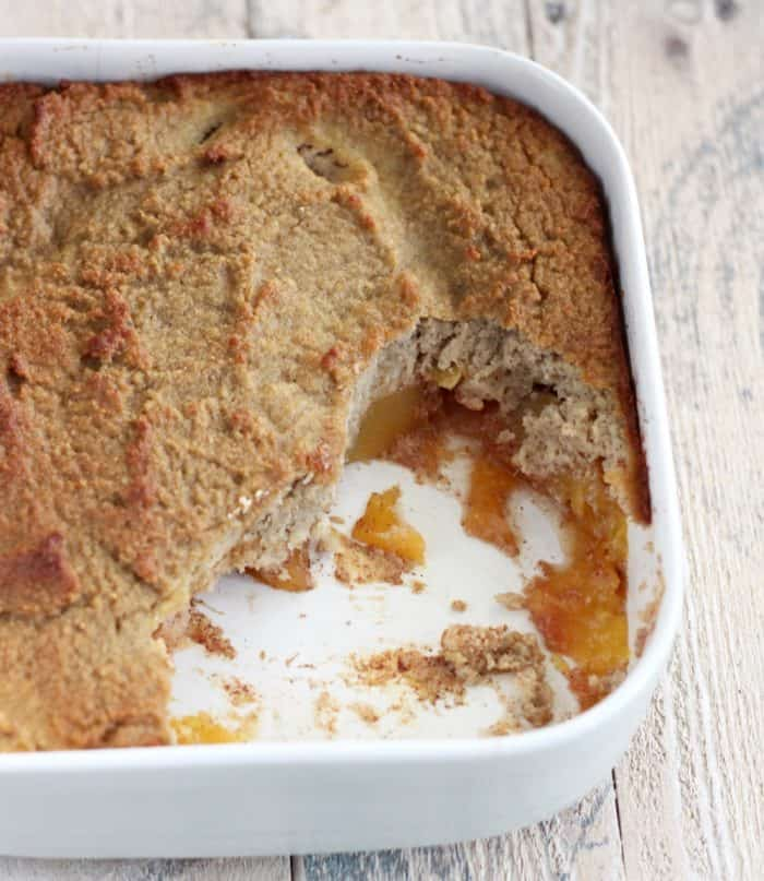 white baking dish with peach cobbler, some scooped out