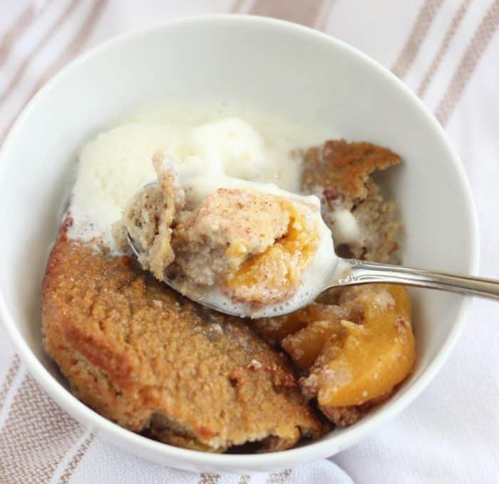 white bowl on brown and white stripe towel with peach cobbler, ice cream, spoon