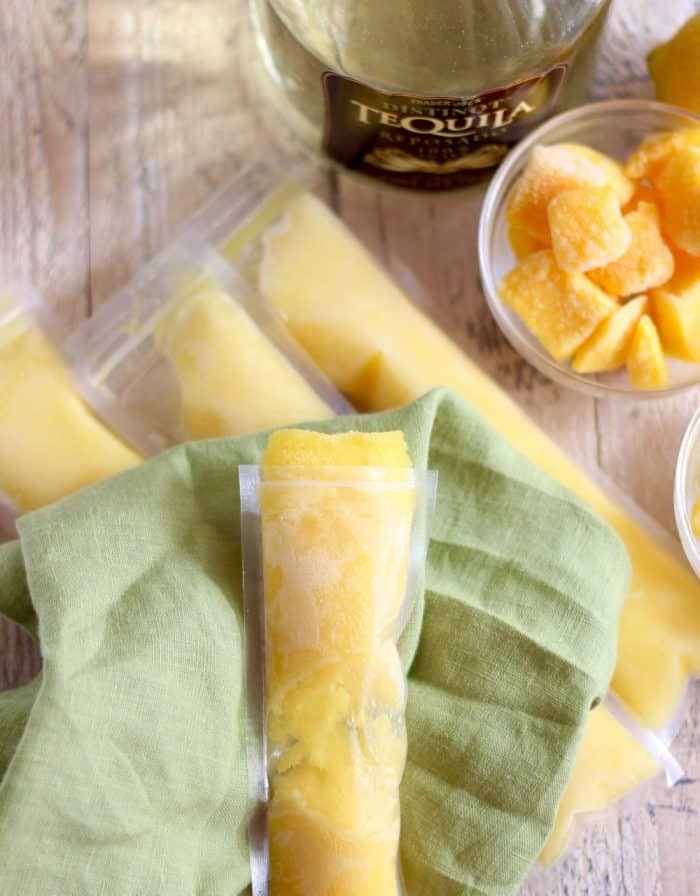 Boozy Mango Pineapple Popsicle on green napkin with other popsicles, tequila, mango