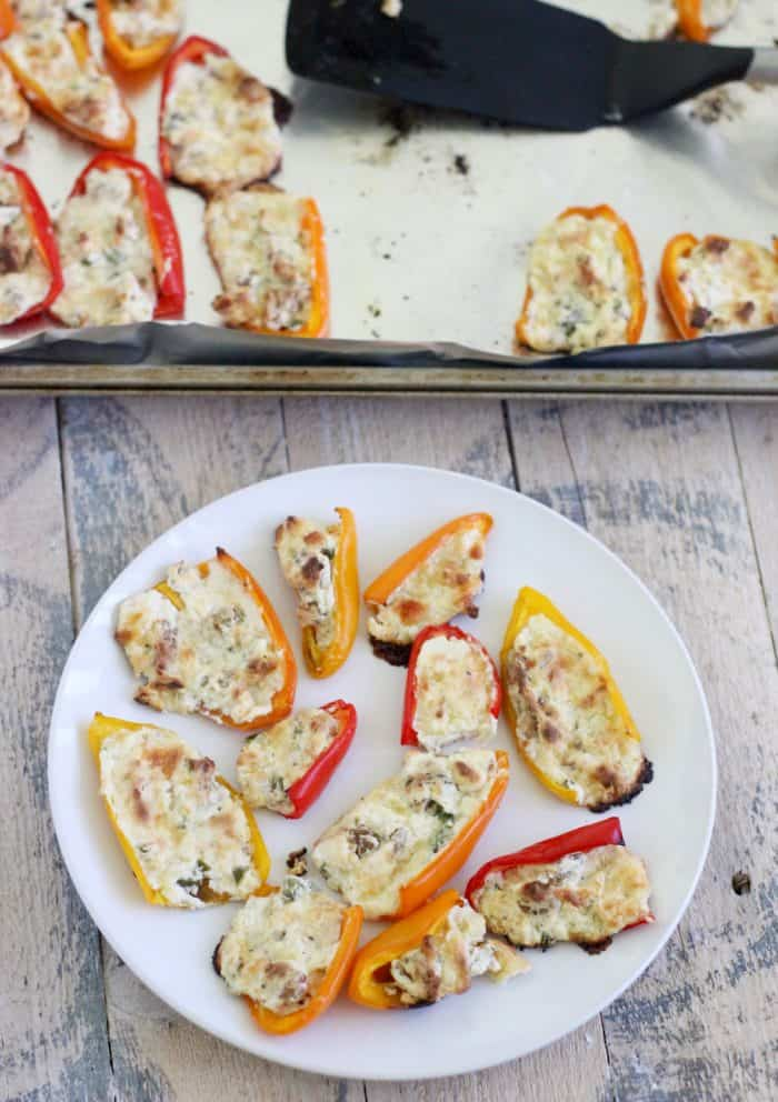 plate of bell peppers stuffed with cream cheese with foil-lined baking sheet and spatula with extra bell peppers