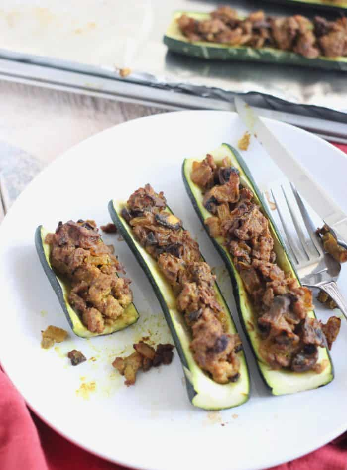 partially eaten Stuffed Zucchini with lamb on white plate, fork and knife