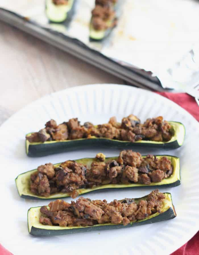 Curry Lamb Stuffed Zucchini on white plate with baking sheet in background