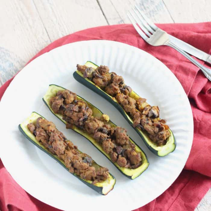 3 Lamb Stuffed Zucchini on a white plate with a red napkin and fork and knife