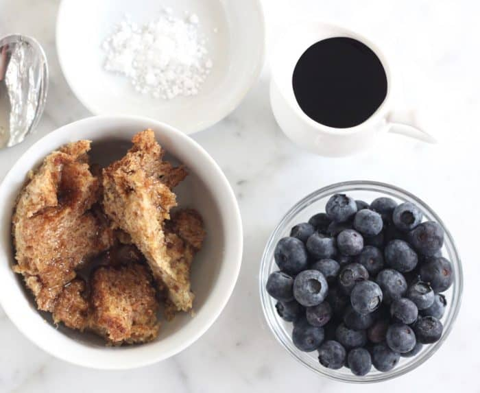 bowl of fresh toast casserole sprinkled with powdered sugar with syrup and blueberries