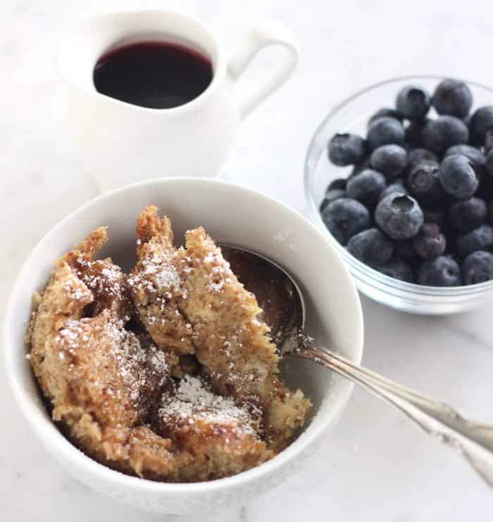bowl of French Toast Casserole with powdered sugar, syrup, and blueberries