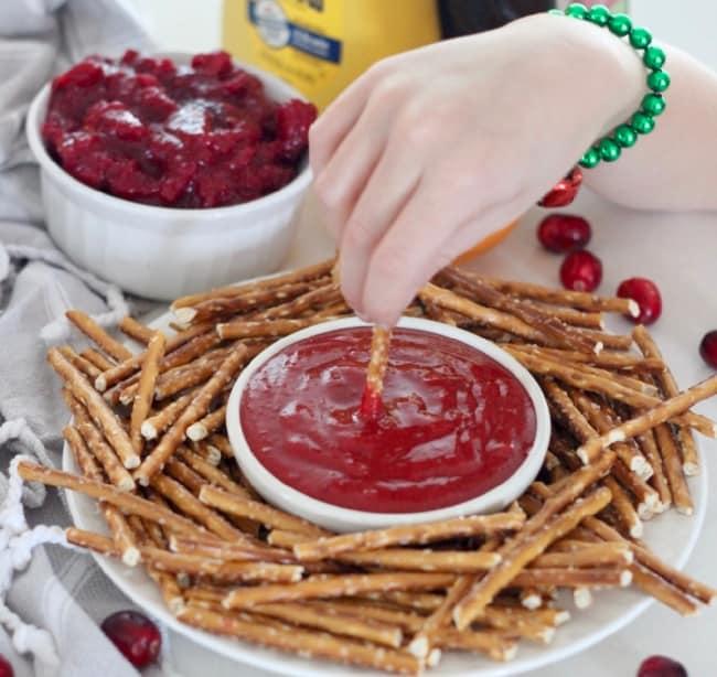 hand dipping a pretzel into cranberry honey mustard sauce