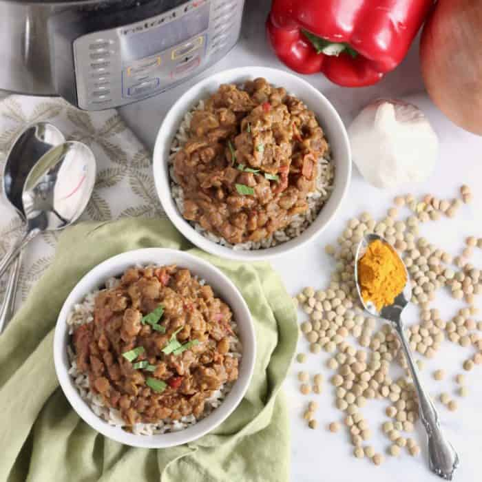 two white bowls of lentil curry on green napkin with silver spoons, green lentils, curry powder, garlic, onion, red bell pepper