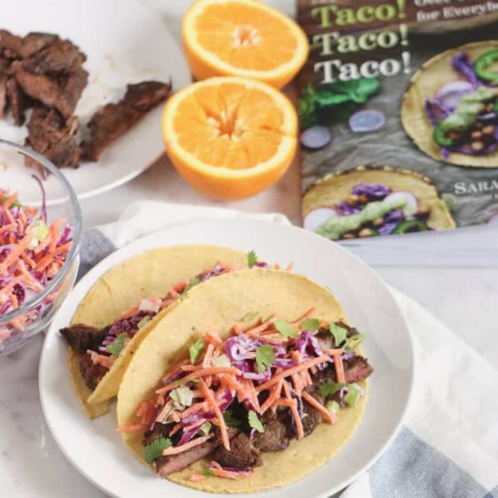 Taco cookbook with two BBQ Skirt Steak Tacos with slaw and steak