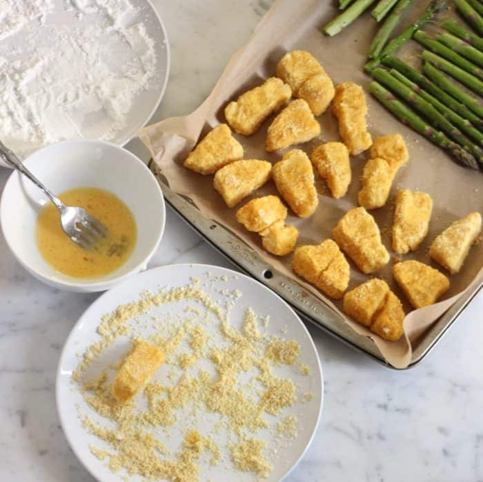 process of breading fish sticks with cornstarch, egg, and almond flour with a baking sheet of breaded fish sticks