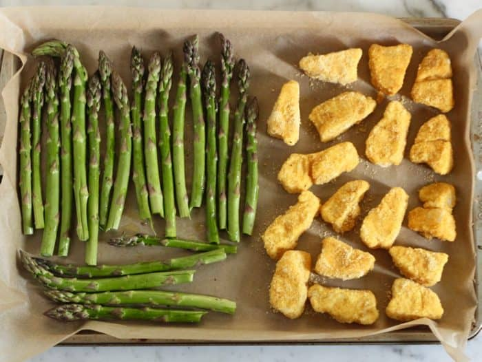prepared baking sheet of uncooked, breaded fish sticks and asparagus